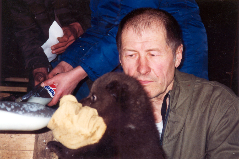В. С. Пажетнов кормит 2,5-месячного медвежонка. Февраль, 2001 г.